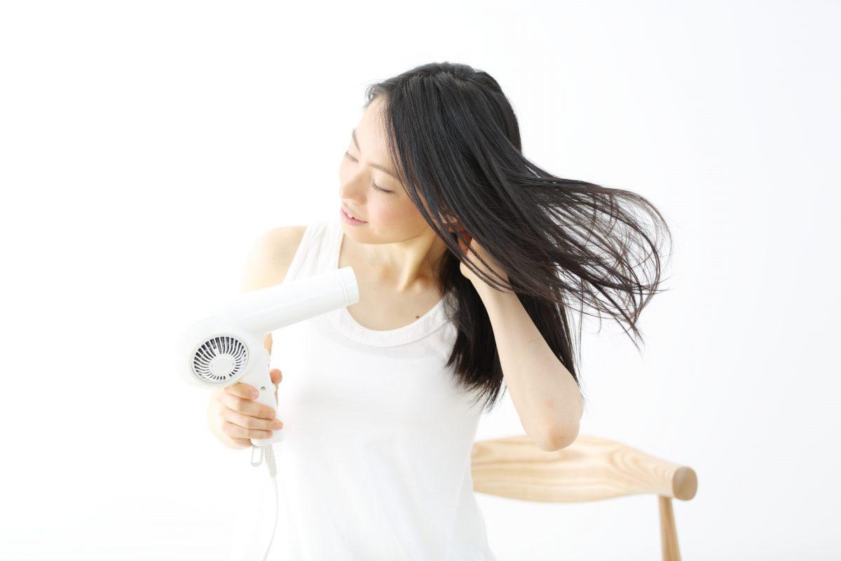 髪をドライヤーで乾かす女性